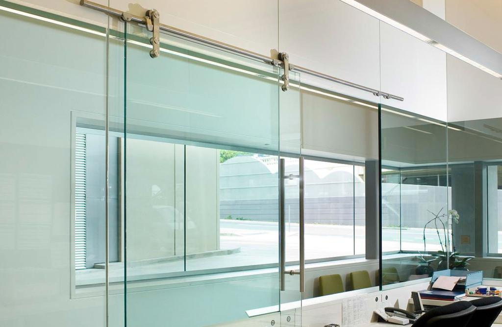 Puerta corredera colgante inox de glasstech for Riel puerta corredera